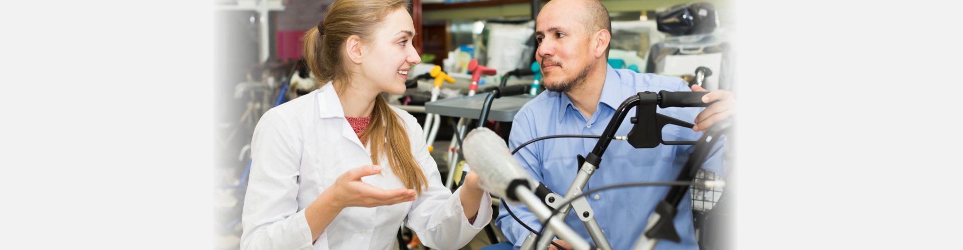 Female consultant offering wheelchair to smiling senior customer